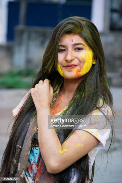 Portrait Of Smiling Young Woman With Powder Paint On Face During Holi