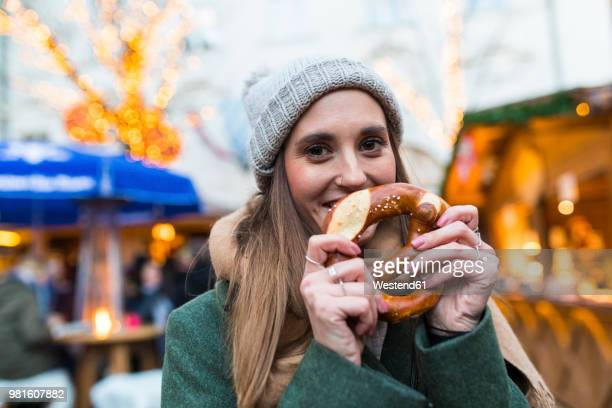 portrait of smiling young woman with pretzel at christmas market - christmas market stock pictures, royalty-free photos & images