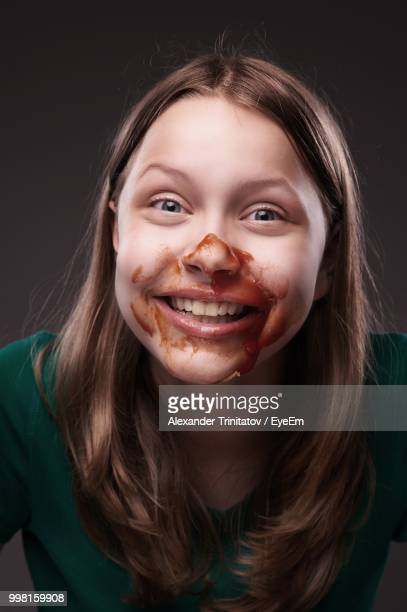 portrait of smiling young woman with sauce on face against black background - sauce stock pictures, royalty-free photos & images