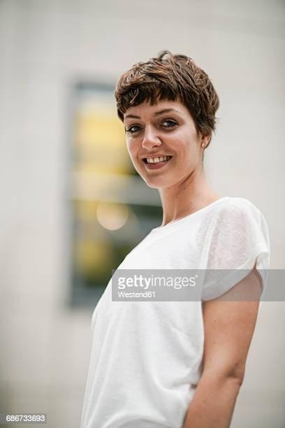 portrait of smiling young woman with short brown hair - kurzhaarschnitt stock-fotos und bilder