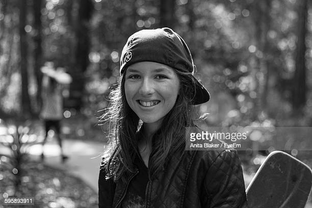 Portrait Of Smiling Young Woman With Skateboards While Standing Against Trees At Park
