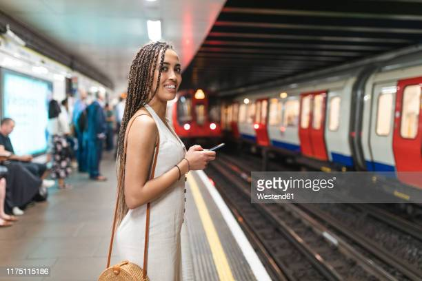 portrait of smiling young woman with smartphone waiting at subway station platform, london, uk - vertical red tube fotografías e imágenes de stock