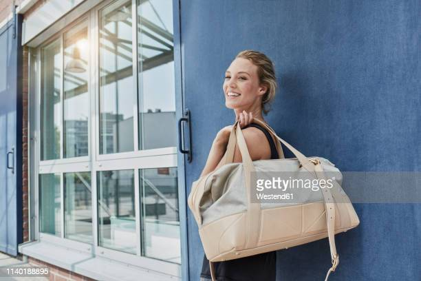 Portrait of smiling young woman with sports bag in front of gym
