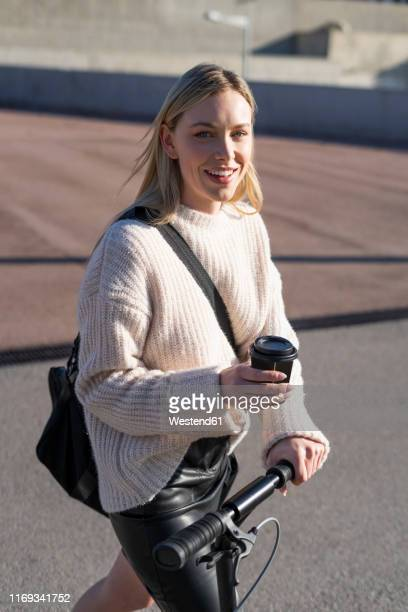 portrait of smiling young woman with sports bag, kick scooter and coffee to go - 斜め掛けバッグ ストックフォトと画像