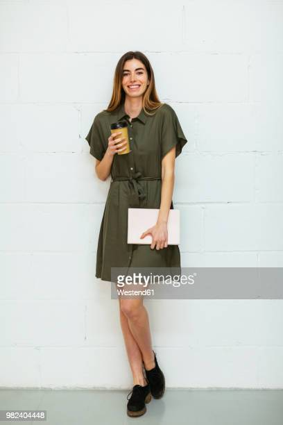 portrait of smiling young woman with tablet and takeaway coffee standing at brick wall - kleid stock-fotos und bilder