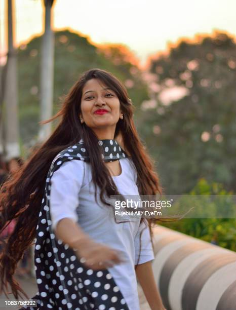 portrait of smiling young woman with tousled hair against trees - guwahati stock photos and pictures
