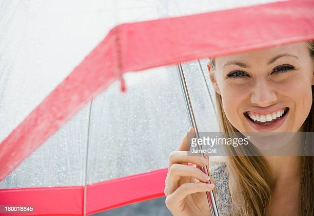 Portrait of smiling young woman with umbrella in rain