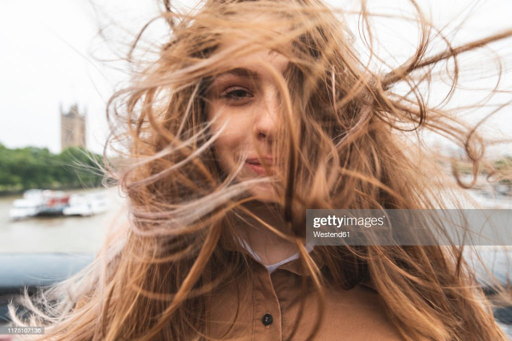 Portrait of smiling young woman with windswept hair, London, UK : Stockfoto