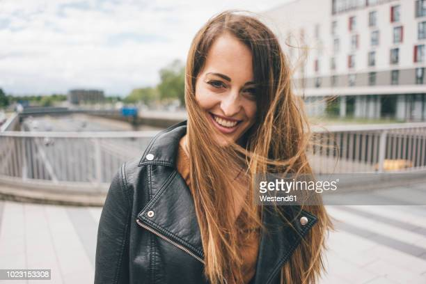 portrait of smiling young woman with windswept hair on motorway bridge - 後ろボケ ストックフォトと画像
