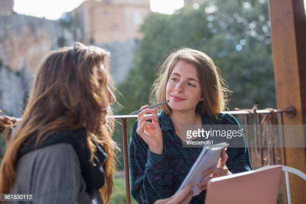 portrait of smiling young woman working on terrace - journalist stock pictures, royalty-free photos & images