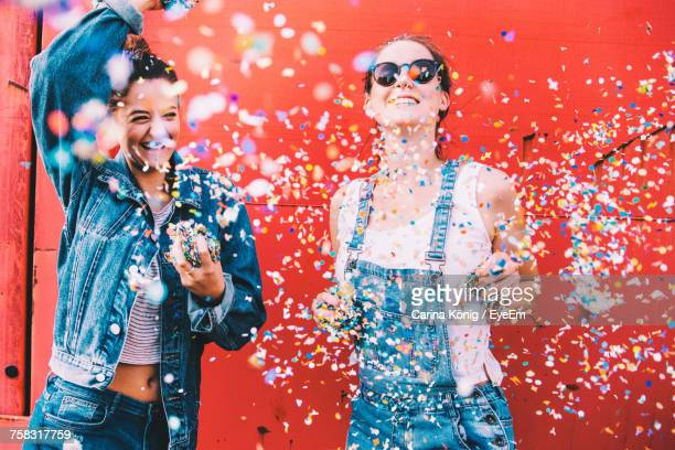 portrait of smiling young women against red wall - festeggiamento foto e immagini stock
