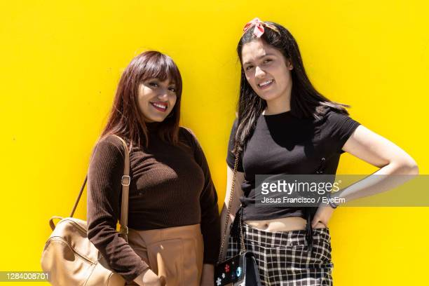 portrait of smiling young women against yellow background - laughing jesus images stock pictures, royalty-free photos & images