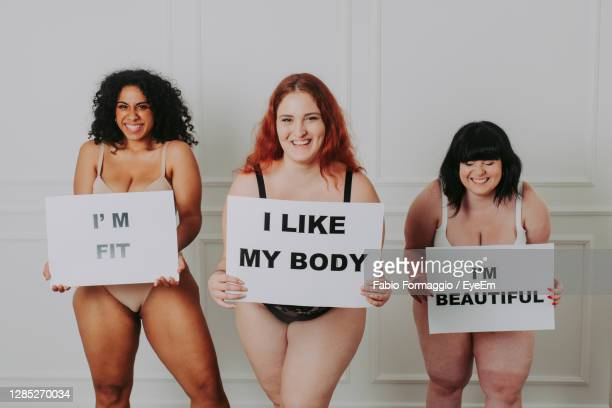 portrait of smiling young women holding placard standing against wall - body positive stock pictures, royalty-free photos & images