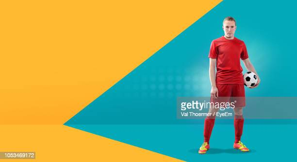 portrait of soccer player with ball standing against colored background - fußballspieler stock-fotos und bilder