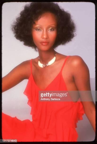 Portrait of Somali-born American fashion model Iman, in a red dress, as she poses against a white background, 1975.