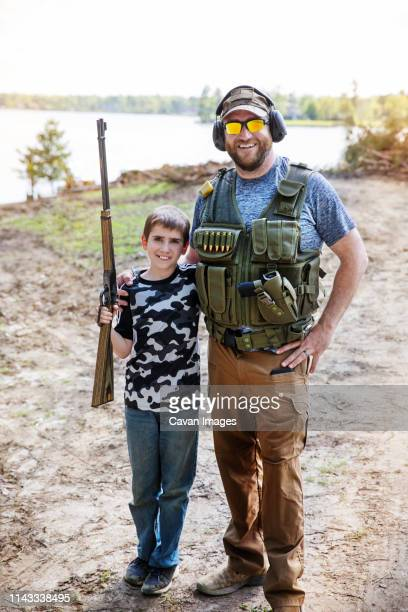portrait of son holding rifle while standing with father on field against sky - hunting stock pictures, royalty-free photos & images