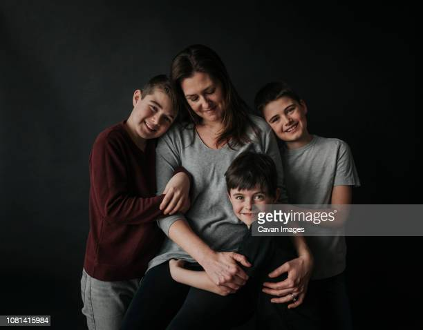 portrait of sons with mother standing against black background - genitore unico foto e immagini stock