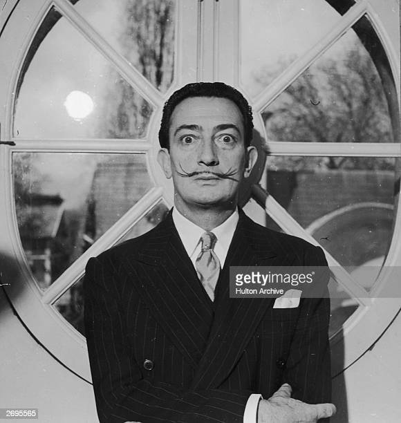 Portrait of Spanish surrealist artist Salvador Dali He is wearing a pinstriped suit and his trademark mustache