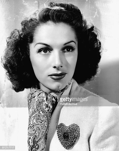 Portrait of Spanishborn American actress Jinx Falkenburg as she wears a white tweed suit pink paisley scarf and heartshaped lapel pin set with a star...