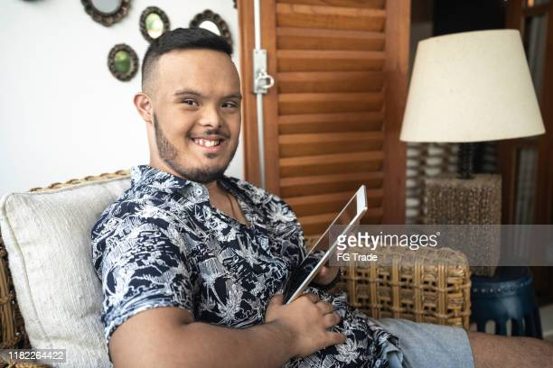 portrait of special needs boy using tablet at home - persons with disabilities stock pictures, royalty-free photos & images