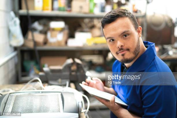 portrait of special needs employee holding a digital tablet in industry - persons with disabilities stock pictures, royalty-free photos & images