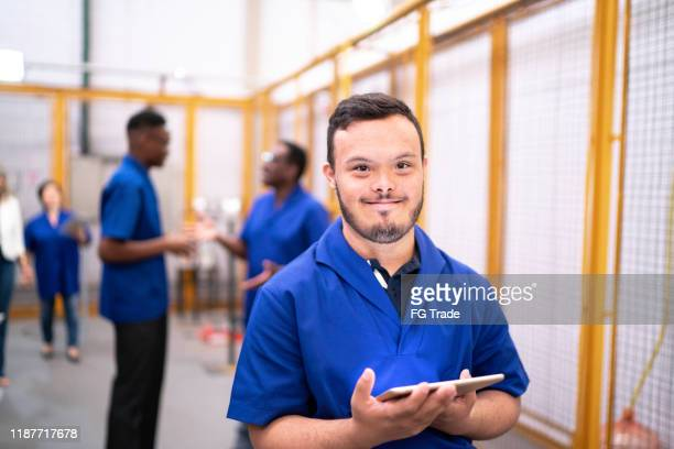 portrait of special needs employee holding digital tablet in industry - down syndrome stock pictures, royalty-free photos & images