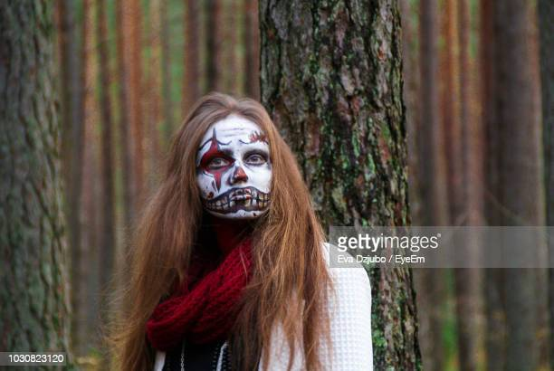portrait of spooky woman with halloween make-up standing in forest - scary clown makeup stock photos and pictures