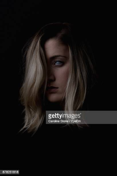 portrait of spooky young woman against black background - scary face stock photos and pictures