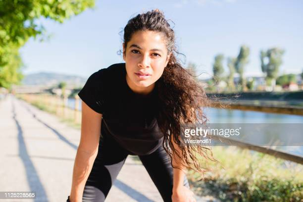 portrait of sportive young woman having a break at the riverside - extra long stock pictures, royalty-free photos & images