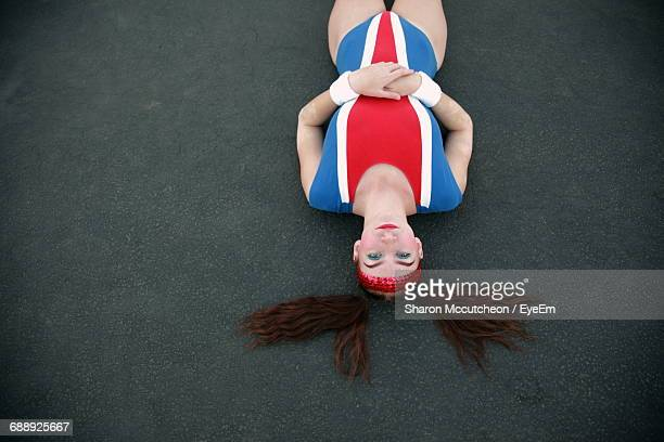 Portrait Of Sports Woman Wearing Old-Fashioned Costume Lying Down On Track