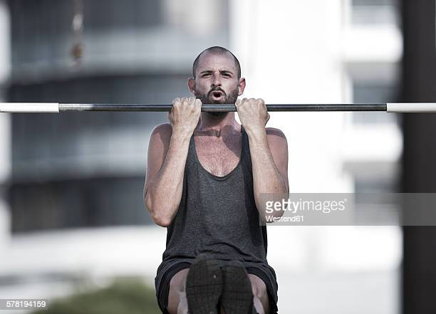 portrait of sportsman doing chin-ups - chin ups stock photos and pictures