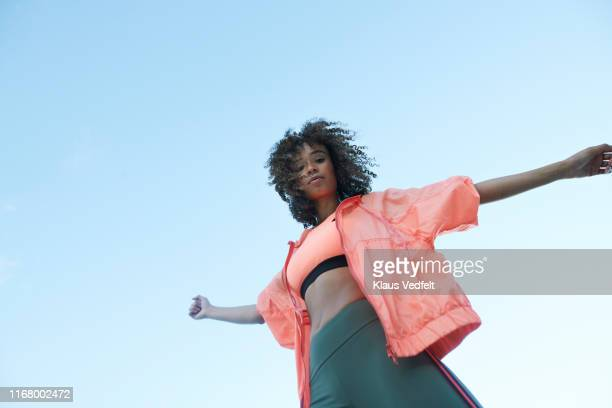 portrait of sportswoman with arms outstretched against clear blue sky - fashion stock pictures, royalty-free photos & images