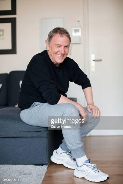 Portrait of sporty senior man sitting on sofa at home