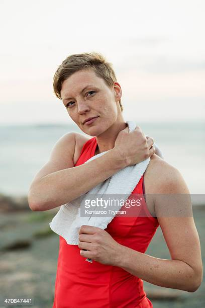 Portrait of sporty woman wiping sweat with towel outdoors