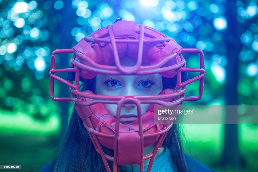 Portrait of staring teenage girl in park wearing red umpire mask : Stock Photo
