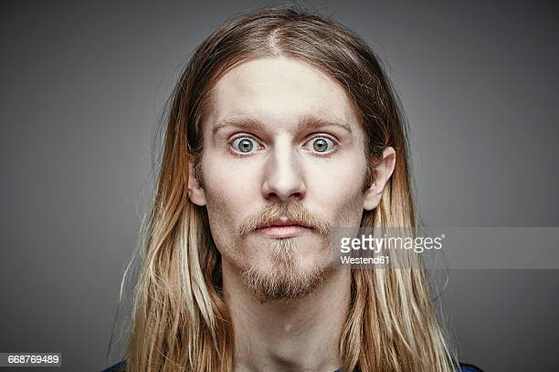 portrait of starring young man with long blond hair and beard - beard stock pictures, royalty-free photos & images