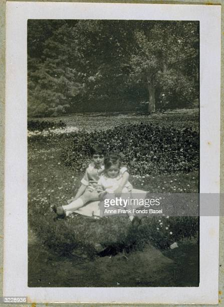 A portrait of Stephan and Bernd Elias cousins of Anne and Margot Frank sitting on a blanket in front of a mound of flowers 1927 The older boy has his...