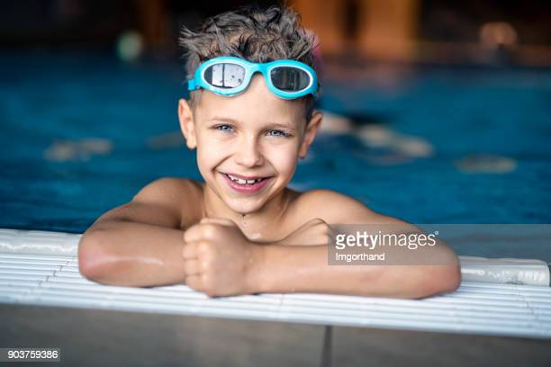 Portrait of strong little boy at the swimming pool