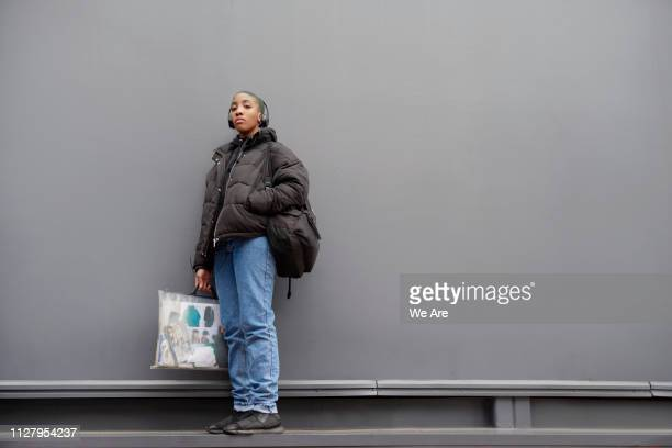 portrait of student holding bag and portfolio. - padded jacket stock pictures, royalty-free photos & images