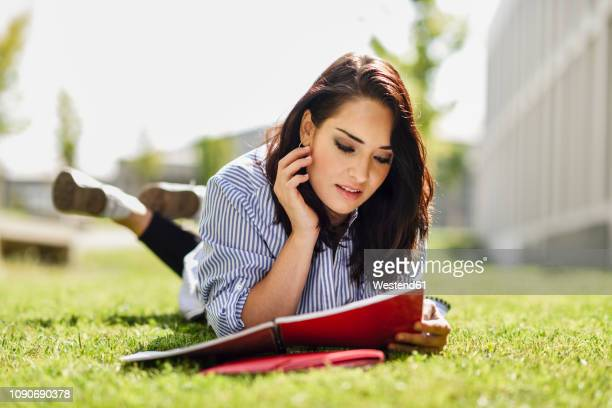 portrait of student lying on lawn reading her notes - lying on front stock pictures, royalty-free photos & images