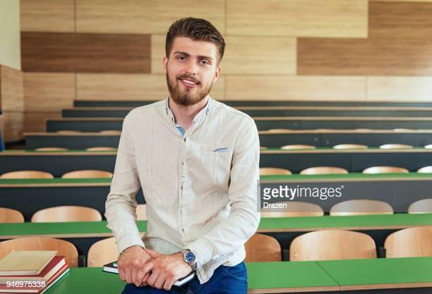 Porträt eines Schülers mit Büchern in leeren Hörsaal