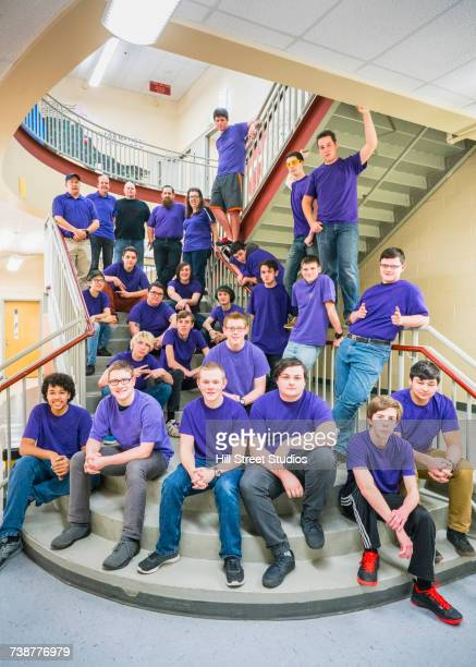 Portrait of students and teachers posing on school staircase