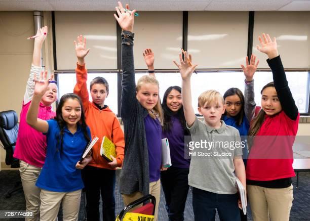portrait of students raising hands in classroom - multiculturalismo foto e immagini stock