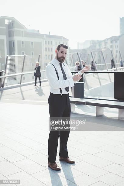 Portrait of stylish businessman fastening shirt cuffs on footbridge