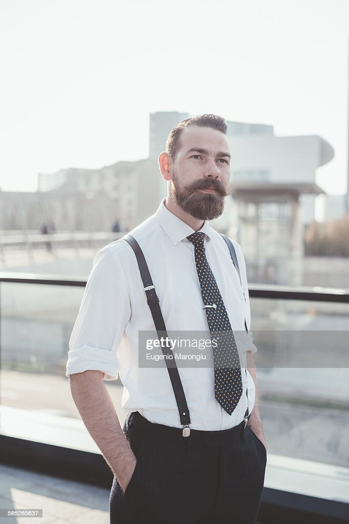 Portrait of stylish businessman with hands in pockets in city : Stock Photo