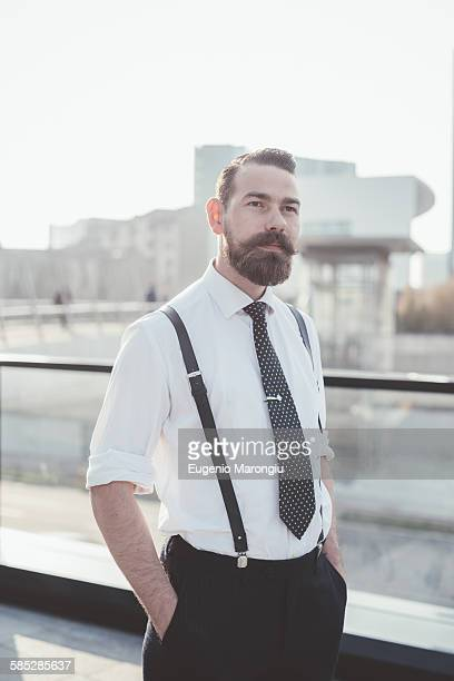 Portrait of stylish businessman with hands in pockets in city