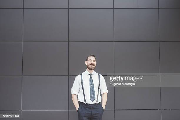 Portrait of stylish businessman with hands in pockets outside office