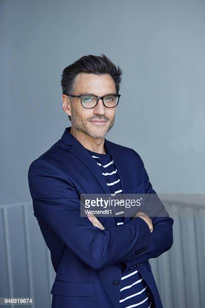 Portrait of stylish businessman with stubble wearing blue suit and glasses