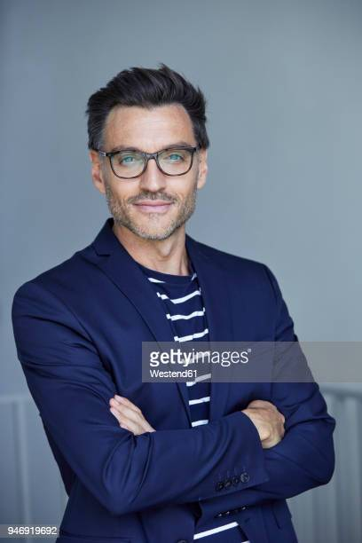 portrait of stylish businessman with stubble wearing blue suit and glasses - striped suit stock pictures, royalty-free photos & images