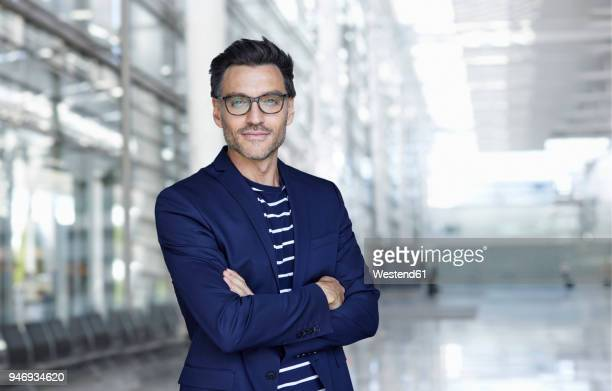 portrait of stylish businessman with stubble wearing blue suit and glasses - anzug stock-fotos und bilder